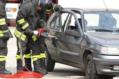 Firefighters with shears open the car doors after a serious car Royalty Free Stock Photo