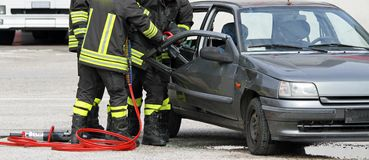Firefighters with shears open the car doors to free the injured Royalty Free Stock Photos