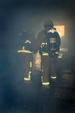 Firefighters in a smoke filled building Stock Photos