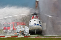 Firefighters in special suits. Extinguish the fire by helicopter Stock Photos