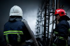 Firefighters spray water. Smoke and buiding after fire royalty free stock photo