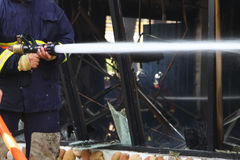 Firefighters spray water to wildfire.  Stock Photography