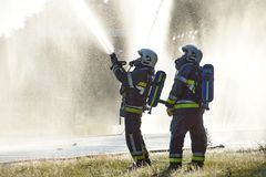 Firefighters spraying against background of waterdrops. Two firemen spraying water using a hose and carrying oxygen tanks Stock Photography