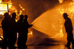 Firefighters spraying burning structure with water Royalty Free Stock Image