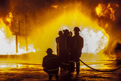 Firefighters spraying down burning structure Stock Photos