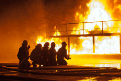 Firefighters spraying down burning structure during firefighting exercise Stock Photography