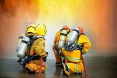 Firefighters spraying high pressure water to fire with copy space, Big bonfire in training, Firefighter wearing a fire suit for royalty free stock image