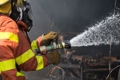 2 firefighters spraying water in fire fighting operation stock image