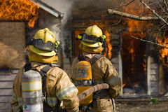Firefighters standing by. Two firefighters standing by with hose at a residential structure fire Royalty Free Stock Photography