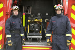 Firefighters standing by the equipment Royalty Free Stock Image
