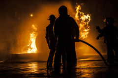 Firefighters standing in a line fighting a fire Stock Image