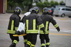 Firefighters with the stretcher after a tragic road accident Stock Photography