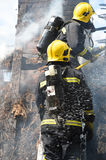 Firefighters tackle a fire on a cottage roof. Royalty Free Stock Photos