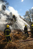 Firefighters tackle a fire in a rural thatch roof cottage Royalty Free Stock Images
