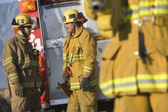 Firefighters Talking With Each Other. Male firefighters talking with each other with colleague in the foreground Stock Image