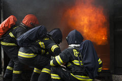 Firefighters. Training - firefighters in burning shipping container Stock Image
