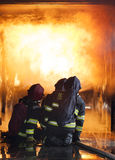 Firefighters. Training - firefighters in burning shipping container Royalty Free Stock Images