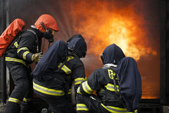 Firefighters. Training - firefighters in burning shipping container Stock Photography