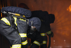 Firefighters. Training - firefighters in burning shipping container Stock Photos