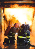 Firefighters. Training - firefighters in burning shipping container Royalty Free Stock Photos