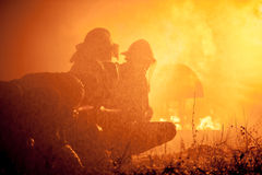 Firefighters training. They try to control fire with water Royalty Free Stock Images