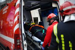 Firefighters transport patient on ambulance. After all  injured patient litter preparation is time to go to hospital Royalty Free Stock Image