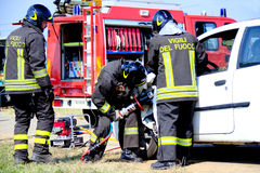 Firefighters use shears on cars. Italian firefighters using hydraulic shears to cut a car during a demonstration for the population. Simulation took place in San Stock Image