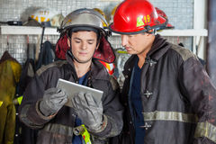 Firefighters Using Digital Tablet At Fire Station Royalty Free Stock Photography