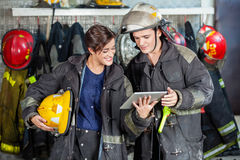 Firefighters Using Digital Tablet At Fire Station. Young male and female firefighters using digital tablet at fire station Royalty Free Stock Photos