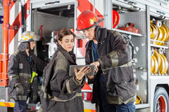 Firefighters Using Tablet Computer Against Truck Royalty Free Stock Photos