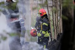 Firefighters using water hoses to extinguish a fire. BUCHAREST, ROMANIA - APRIL 17: Firefighters try to extinguish with water a fire that spread across an Stock Image