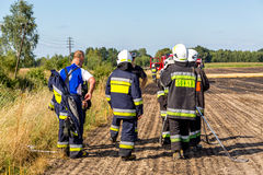 Firefighters walking on the field on fire Stock Photography