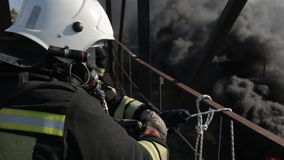 Firefighters wearing gas masks work at high stock video