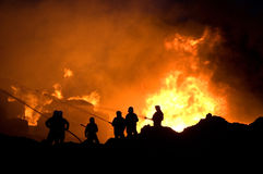 Firefighters at work. Firefighters trying to control a fire Stock Image