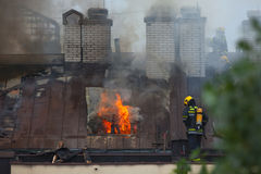 Firefighters at work on extinguishing the real fire. Fire fighting in reality on the roof of eight floor building, which lasted up to eight hours with six teams Royalty Free Stock Images