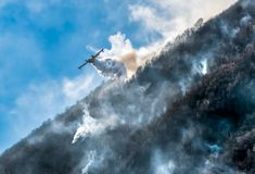 Firefighting Aircraft dropping the water for fighting a fire on mountain.  stock photography