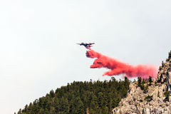 Firefighting aircraft dumping retardant. Firefighting aircraft dumping red fire retardant chemical over forest during Montana fire fighting effort to help stock images