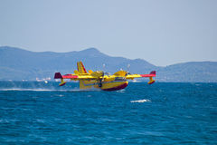 Firefighting airplane taking water from sea Royalty Free Stock Images