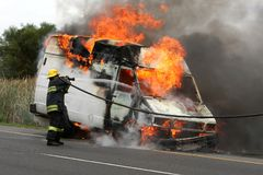 Firefighting and Burning Vehicle Stock Photo