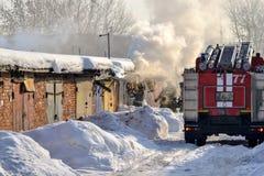 firefighting En brandlastbil och brandmän på arbete En raddarök timmar liggandesäsongvinter Ryssland royaltyfri fotografi