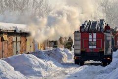 firefighting En brandlastbil och brandmän på arbete En raddarök timmar liggandesäsongvinter Ryssland royaltyfria bilder