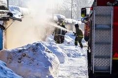 firefighting En brandlastbil och brandmän på arbete En raddarök timmar liggandesäsongvinter Ryssland royaltyfri foto