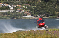 Firefighting helicopter. On a collecting water in the river Royalty Free Stock Photography