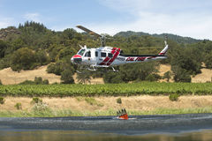 Firefighting helicopter fills water bucket Stock Photography