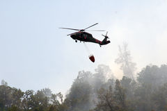 Firefighting helicopter flies over burned land Royalty Free Stock Image