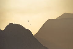 Firefighting helicopter flying above mountains Stock Images