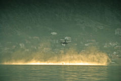 Firefighting helicopter flying close above water Stock Photography