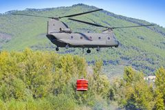 Firefighting helicopter of the Italian army is carrying a metal bucket full of water to extinguish a fire in a mountain.  stock images