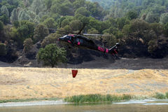 Firefighting helicopter refills water bucket Royalty Free Stock Photography