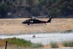 Firefighting helicopter refills water bucket Stock Image